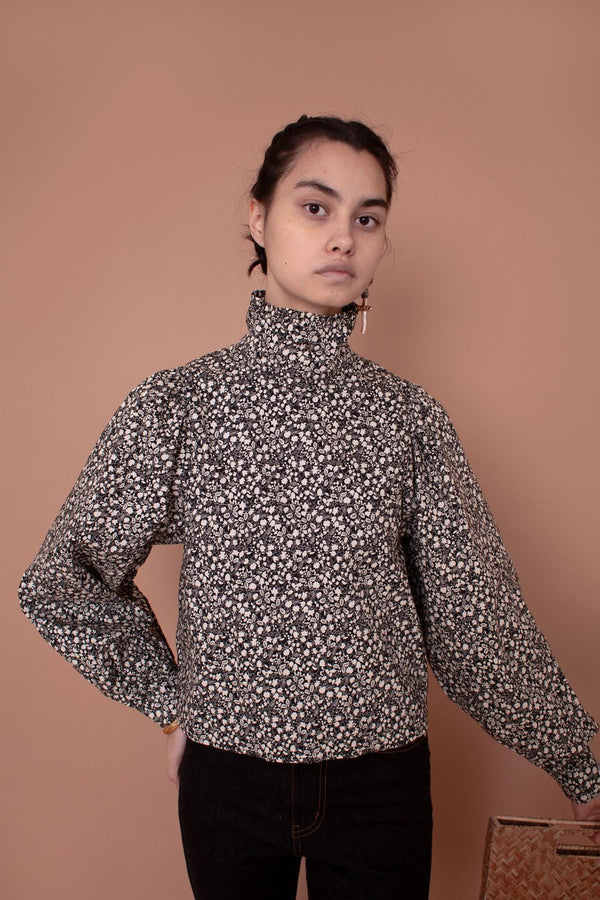 The Carnation Top is a slightly cropped straight cut shirt with a high pleated neck and large voluminous sleeves with a gathered shoulder and cuff. Featuring elegant button fastening on the back of the neck and cuff. Made from 100% cotton in a white floral print on a black base. Enjoy a moment of elegance in the Carnation Top designed by Meadows.