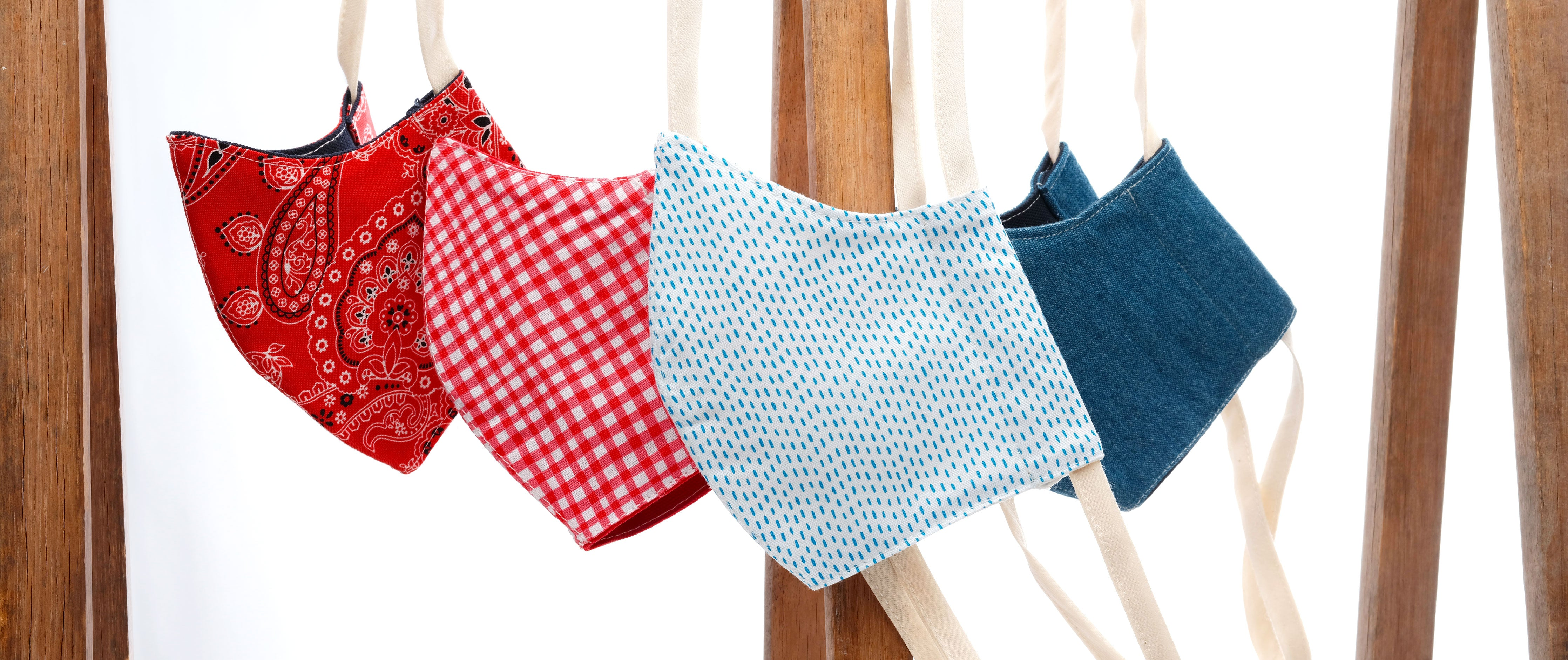 4 hanging faces masks. From left to right, red bandana, strawberry gingham, white blue dash, and denim.