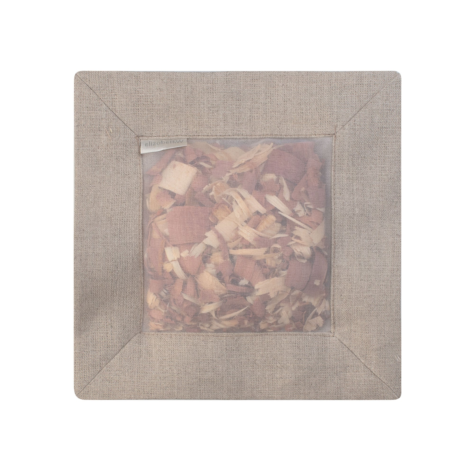"Cedar filled inside of a ""natural"" colored square sachet with a transparent screen"