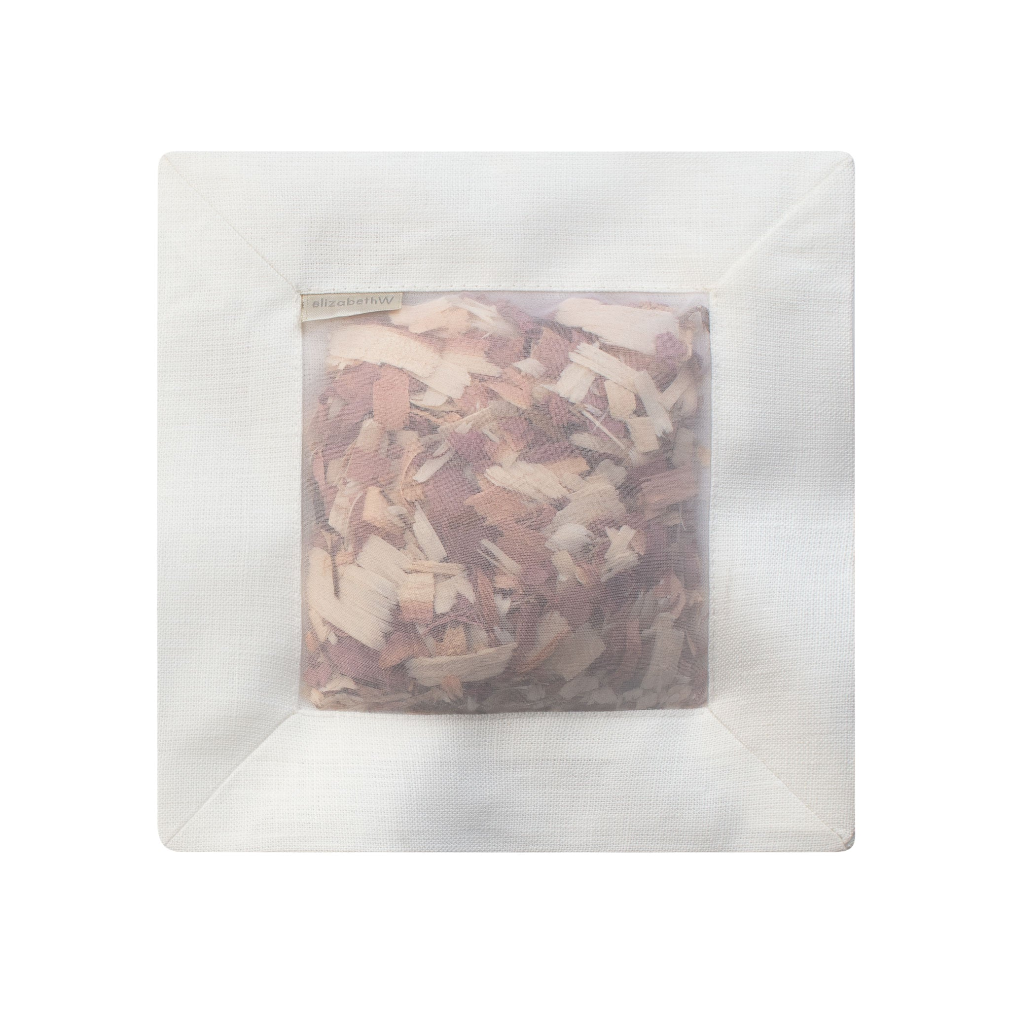 Cedar filled inside of an ivory colored square sachet with a transparent screen