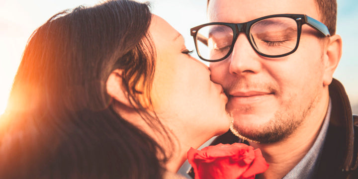 Valentines day date couple woman kissing man with black prescription glasses