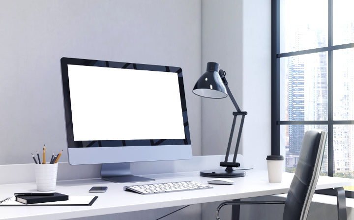 Office desk with working lamp, bright computer screen and sunlight