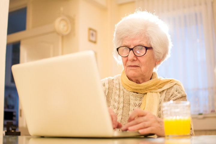 old woman on computer with her outdated and out-of-fashion prescription glasses