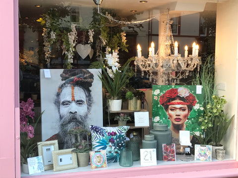 Shop window full of home decor accessories inlcuding wall art, photo frames, candleholders and gifts