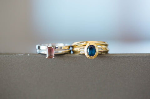 (Amy's ring left, emerald cut watermelon tourmaline, four claw set in platinum - Emily's ring, oval cut sapphire in rub-over setting, with baguette diamonds in yellow gold)