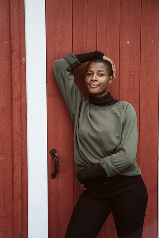 green crewneck sweater in front of a barn