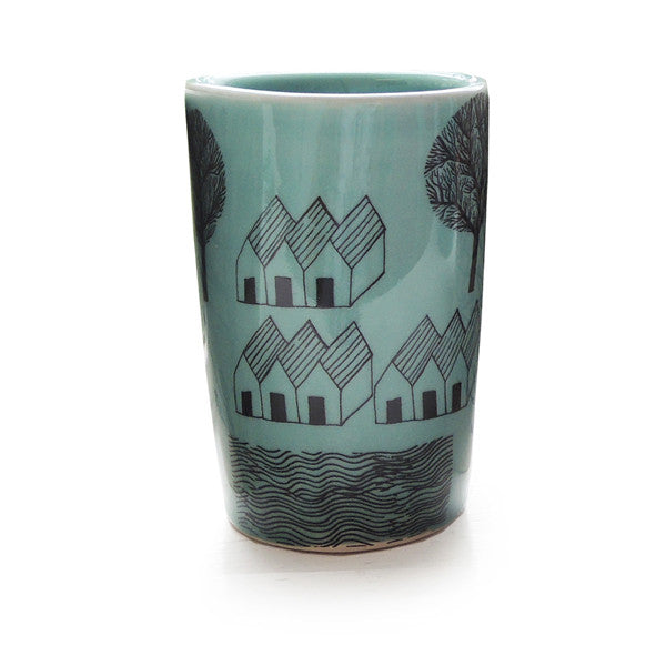 Lush Designs hand-made ceramic, teal glazed small beaker with design of houses, trees and water