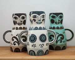 three printed vases, brown, blue and green, shaped like women with hands on hips