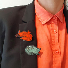 close up of enamel fox badge and cat pin on black lapel blazer worn with orange-red shirt
