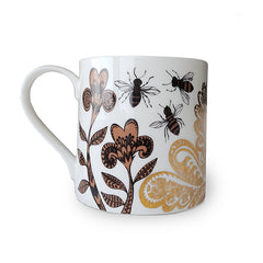 Mug printed with pattern of flowers and bees and gold swirls