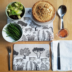 Table setting of wild boar table mats with a mushroom pie, glass of wine and vegetables