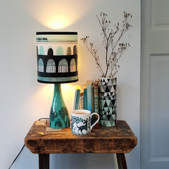 Blue green shade with drawing of Docklands Light Railway train print shown on jade and black printed ceramic lamp base