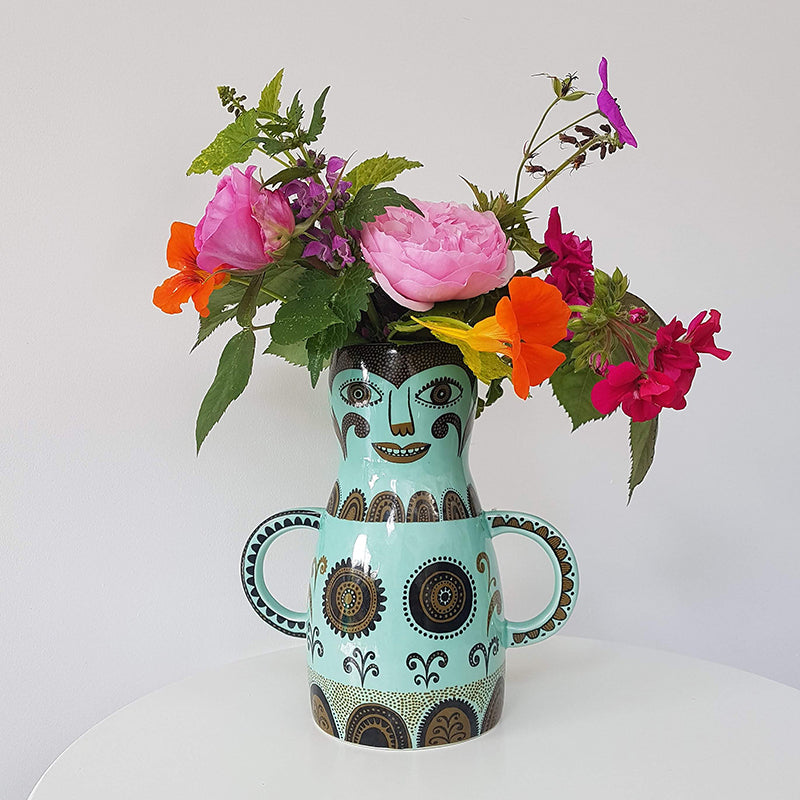 Lush Designs highly decorative light green vase shaped like a woman with hands on hips containing brilliant pink, red, orange and purple flowers