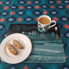A snack of  2 biscotti and a mug of coffee on a mat with a landscape print in dark blue-greens on an african print table cloth