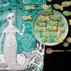 Mermaid print tea towel with a plate of fish-shaped biscuits