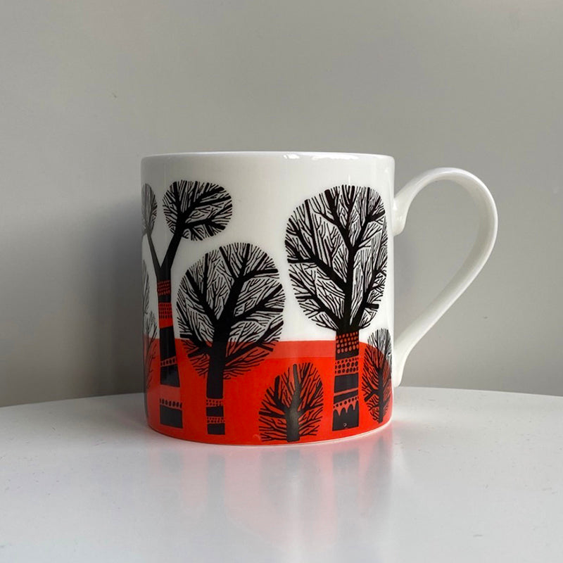 Lush Designs bone china mug printed with a pattern of leafless black trees against a brilliant orange-red ground