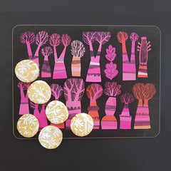Lush Designs table mat in black with hot pink and orange tree design shown with home made patterned biscuits