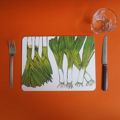 Table mat printed with leeks on an orange table set with fork, knife and glass