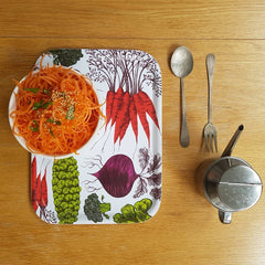 Lush designs tray printed with vegetables on it a bowl of carrot salad next to it a pewter fork and spoon and tin oil pourer