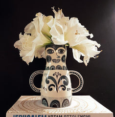 Lady-shaped vase with handles like arms with large white flowers in it that look like an extravagant hat