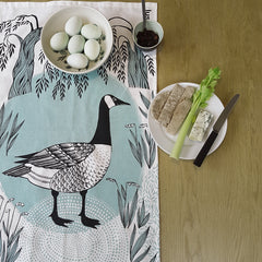 Lush Designs Goose print tea towel with pale blue eggs in a bowl and a cheese and celery snack on a plate
