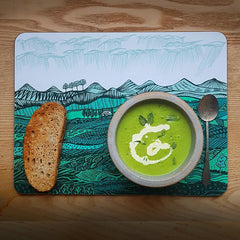 Mat depicting landscape of green hills with green pea soup and toast and a pewter spoonst