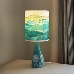 Lush Designs ceramic lamp base in jade green with white tree print shown with shade that is printed with a landscape of fields and hills in shades of green