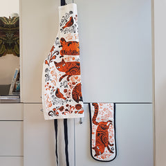 apron and bag hanging on a door, both printed with pattern of orange and black patterned cats, flowers and birds