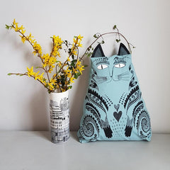 Lush Designs blue cat-shaped kitty cushion with vase of yellow flowers