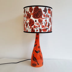 Lush Designs lamp in red-orange decorated with small birds shown with shade printed with shrubs and gardening tools