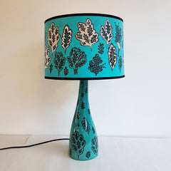 Lush Designs Turquoise printed shade with oak trees and leaves on a matching ceramic lamp base
