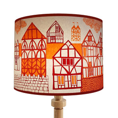 Lush Designs lampshade on a wooden lamp base, printed with half-timbered houses in orange and red