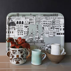Tray with graphic print of a sailing ship on the river thames, with a funny face plant pot, red plant and two little jugs