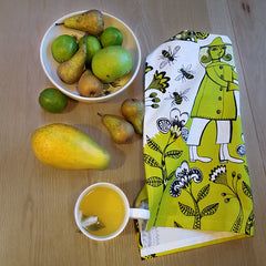 Lush Designs Beekeeper print tea towel next to green and yellow fruit