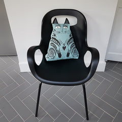 Lush Designs cat-shaped cushion on black modern chair