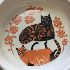 Lush designs cat bowl, the inside with a print of two recumbent cats in orange and black