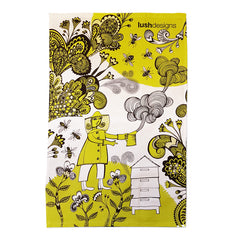 Lush Designs lime green and black print on a tea towel featuring beekeeper smoking her hive and bees in a garden