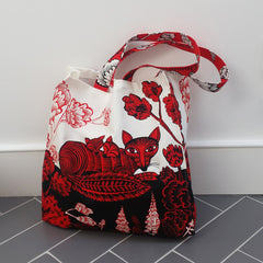 Red and Black printed Fox and cubs bag sitting on the floor