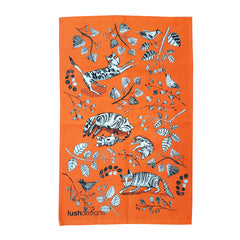 Tea towel with black and white cats and kittens on an orange background