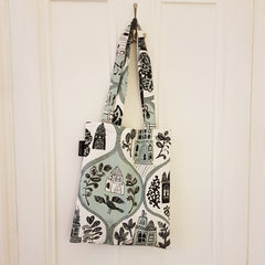 Lush Designs mini tote-bag with teal and black print of little houses, trees and animals hanging on the back of a door.