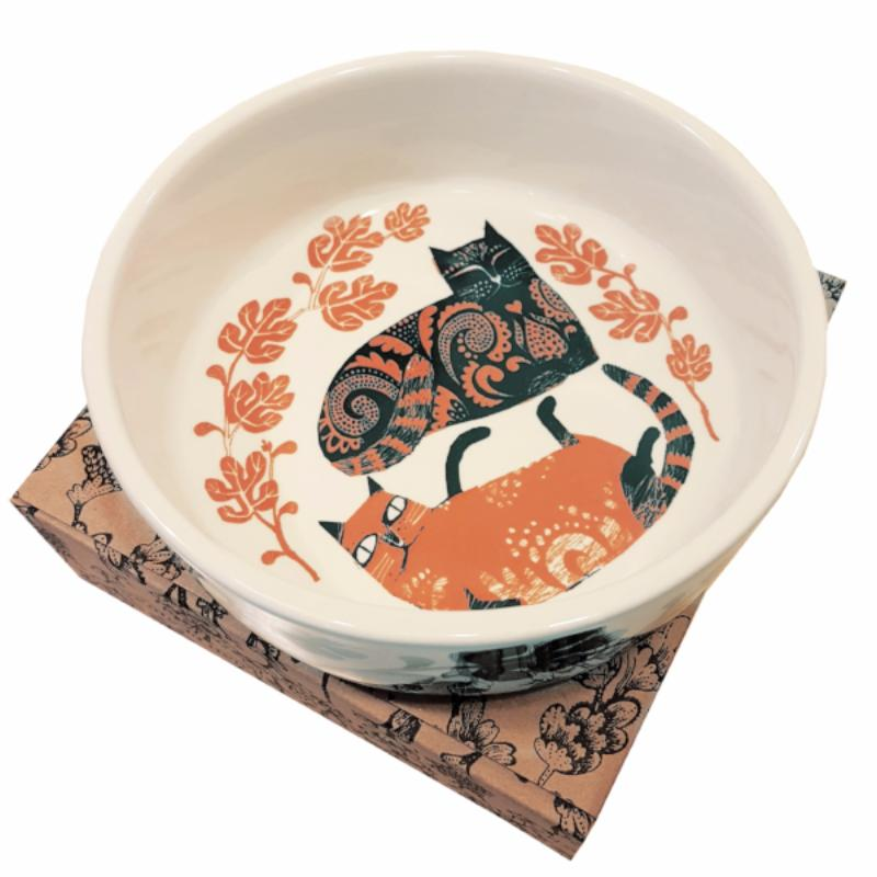 Lush designs orange and black cat bowl with two cats illustrated on it, sitting on a gift box