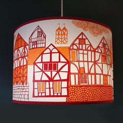 Lush Designs lampshade printed with a picture of old-fashioned buildings in red and orange, pictured against a very dark blue wall