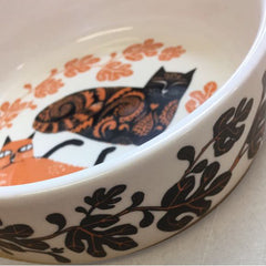 Lush Designs cat feeding bowl pictured from the side showing a glimpse of two orange and black cats, the sides of the bowl decorated with fig leaves