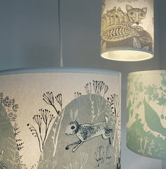 Lush Designs rabbit print shade lit up and hanging with fox and bird lampshades in a group