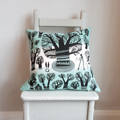 Lush Designs tree print cushion with silhouettes of trees and garden tools in black on teal and white