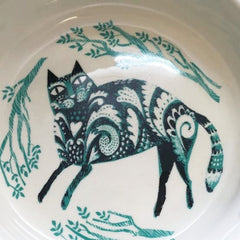 Picture of inside of cat feeding bowl printed with recumbent cat in black and turquoise