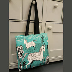 Lush Designs unicorn print bag in turquoise hanging on a drawer knob