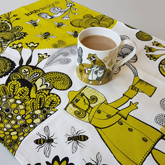 Lush designs Beekeeper and bee print flowery tea towel in yellow-green pictured with beekeeper print mug of tea