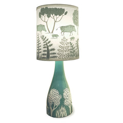 jade glazed ceramic lamp base with white print of trees with shade printed with wild boars in duck egg blue