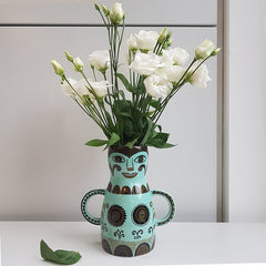 green lady-shaped vase with a bunch of white flowers in it